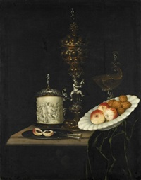 a still life of apples and walnuts in a ceramic dish, a silver and gilt cup and cover, a silver and gilt nautilus shell tazza, and other utensils on a table partly draped with a green cloth by georg hainz