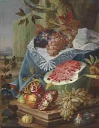 a watermelon, a pomegranate and figs, with grapes on a draped plinth, in a landscape by maximilian pfeiler