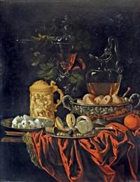 nature morte avec coupe d'orfèvrerie, pichet en verre, citron, pâtisserie et chope en ivoire sur un entablement de pierre au drapé rouge by georg hainz