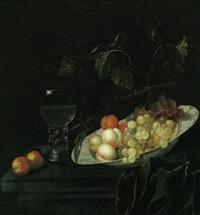 pfirsiche und weintrauben in einer wan li-schale sowie ein gefülltes weinglas by georg hainz