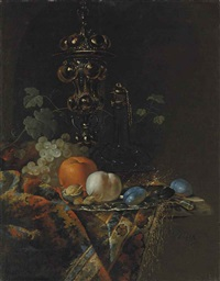 an orange, a peach, plums, hazelnuts and a walnut on a silver plate, before a glass decanter, grapes, a knife and a silver gilt cup and cover, on a partly draped ledge by barend van der meer