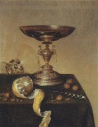 a silver tazza, an upturned roemer, a partly peeled lemon, a knife and hazelnuts on a draped table by maerten boelema de stomme