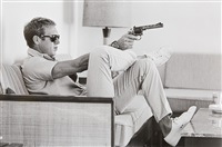 steve mcqueen aims a pistol in his living room by john dominis
