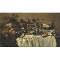 a gilt cup and cover, an overturned pewter jug, fruit, a ham on a pewter plate, three berkmeyer glasses on a pewter plate, a salt, a porcelain mustard pot, a knife and a partly peeled lemon on a table by cornelis cruys