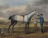 a grey racehorse held by a jockey, with a lad holding up a gold cup, at newmarket by john wootton