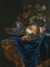 still life with a melon and a peach on a silver platter, together with a glass bowl of grapes and a tray of glassware on a marble table top by christian berentz
