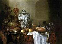 stilleben mit einer ming-vase, zwei pokalen, zinngeschirr, einem gefüllten weinglas sowie einem schinken, weintrauben und pfirsichen auf einem kostbaren orientteppich by cornelis cruys