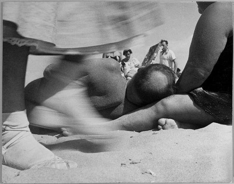 coney island man lying on beach by leon levinstein