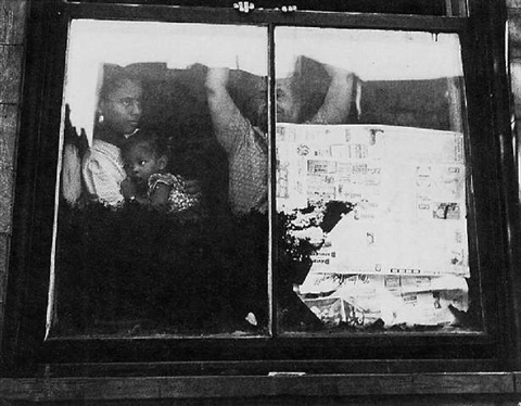 negro family in window by leon levinstein