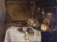 a still life with a roemer, a tall wine-glass, a nautilus cup, pewter plates, lemons, a knife and other objects, all arranged on a partly-draped table by maerten boelema de stomme