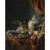 a blue and white faceted vase, a rose and walnuts on a pewter plate, a wan-li kraak porcelain bowl, a silver wine cooler, a wineglass, a glass, a lemon and roses on a table draped with a carpet by joseph de bray