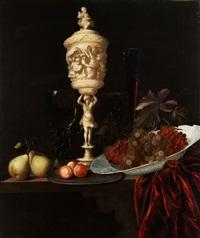 stilleben mit elfenbeinpokal zwischen früchten und einem porzellanteller mit trauben by georg hainz