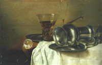 an overturned pewter ewer on a plate, a wineglass, and a peeled lemon on a partly draped table by gerrit willemsz heda