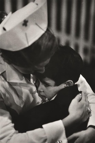child survivor from road accident being comforted by red cross nurse by w eugene smith