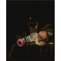 still life with a peeled lemon and an orange in a blue and white porcelain bowl, a roemer, a tall wine glass, a rose and other objects on a draped table by gillis jacobz van hulsdonck