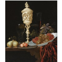 a still life with an ivory carved cup and cover, a roemer, pears, prunes on a pewter plate, grapes in a porcelain wan-li bowl, a flute-glass and a tazza, all on a wooden ledge draped with a red velvet by georg hainz