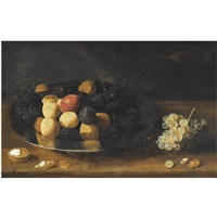 a still life with plums on a silver tazza, together with grapes and a walnut, all on a wooden table by gillis jacobz van hulsdonck