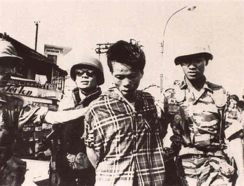 vietcong prisoner being led soldiers with prisoner executioner holstering pistol and others by eddie adams