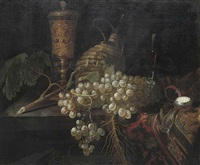 an elaborately decorated vase, a pocket watch, grapes, a carafe and a glass cup on a partially draped table by pieter gerritsz van roestraten