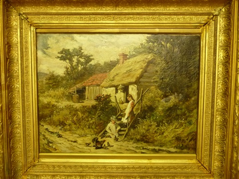 two children feeding chickens beside a thatched cottage by john emms