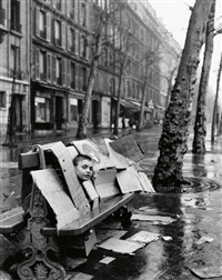 a boy behind a bench and boxes by robert doisneau