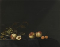 still life of grapes, peaches, apricots and walnuts, all upon a table draped in a dark fabric by evert van aelst