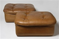 a pair of leather ottomans by airborne