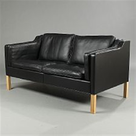 A Two Seater Sofa With Oak Legs Upholstered With Black Leather By