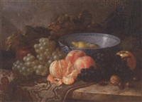 grapes, peaches, oranges, a lemon, nuts, a pomegranate and a ceramic bowl, on a carpet-draped table by r. m. baily