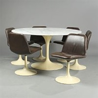 a circular table with a marble top and six swivel chairs of brown leather by eero saarinen