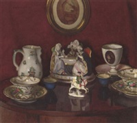 still life of figurines and china on a polished table by istvan zador
