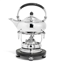 hammered sterling silver kettle on stand, with stylized ornamentation. handle, stand and feet of carved ebony. georg jensen anno by georg jensen (co.)