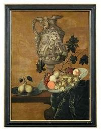 prunkkanne mit figürlichem reliefdekor sowie fayenceschale und zinnteller mit früchten auf einer tischplatte vor lehmfarbenem hintergrund by georg hainz