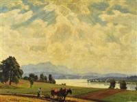 ein bauer bestellt mit seinem zweispännigen pferdepflug den acker mit blick auf einen oberbayerischen bergsee by robert kämmerer