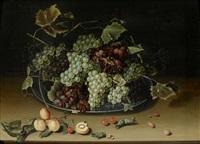 früchtestilleben mit trauben auf einem zinnteller sowie aprikosen, kirschen und nüssen auf einem tisch by isaac soreau