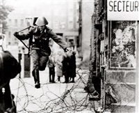 east german border guard konrad schumann jumping over barbed wire line to west berlin. august 15, 1961 by peter leibing