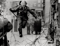 east german border guard konrad schumann jumping over barbed wire line to west berlin. august 15 by peter leibing