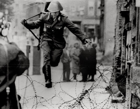 east german border guard konrad schumann jumping over barbed wire line to west berlin august 15 by peter leibing