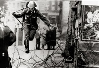 east german border guard konrad schumann jumping over barbed wire line to west berlin by peter leibing