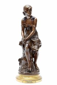 een bronzen sculptuur van een jonge vrouw zittend op een rots,