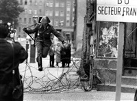 east german border guard konrad schumann jumping over barbed wire line to west-berlin. august 15 by klaus lehnartz