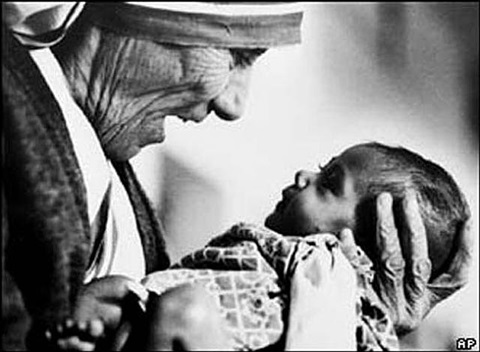 mother teresa cradling an armless baby orphan at her order's orphanage in calcutta, india by eddie adams