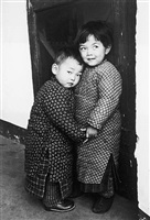 a child protects her brother from a stranger with a camera, tsingtao, china by carl mydans