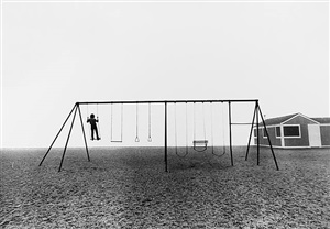 boy standing on swing by larry silver
