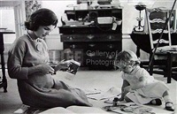 jacqueline kennedy, wife of senator with scissors cutting out newspaper clippings next to open scrapbook as her young daughter caroline toys with the applicator from a glue bottle, at home, hyannis port, ma by alfred eisenstaedt
