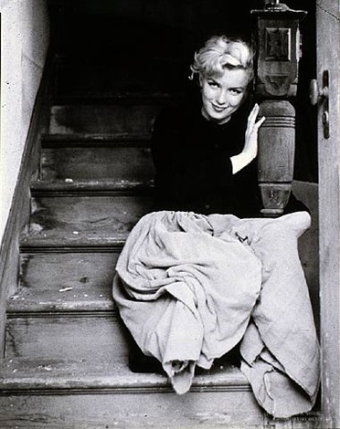 marilyn monroe, seated on a wooden staircase wearing a peasant skirt by milton h. greene