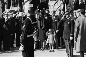 john f. kennedy jr. saluting his father's coffin, november 25, 1963 with ted kennedy, jacqueline kennedy, rose kennedy, peter lawford, and robert f. kennedy in background by stan stearns
