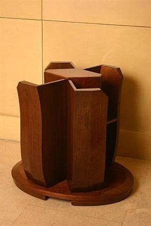 guéridon bibliothèque en noyer présentant quatre ailettes formant étagères, reposant sur une base ovale débordante / walnut side table with shelves resting on an oval base by pierre chareau