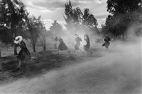 young mennonite women fleeing a cloud of dust, durango, mexico by larry towell