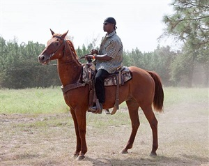 <!--11-->black cowboys: trail rides: trail riders on horseback: young man with du-rag, bynes trail ride, swainsboro, georgia by andrea robbins and max becher